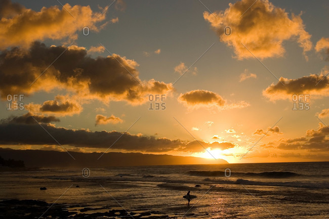 A solitary surfer enters the water as the sun sets in Hawaii
