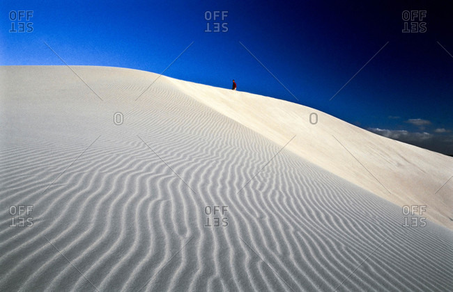 A distant hiker crests a pure white sand dune in the late afternoon