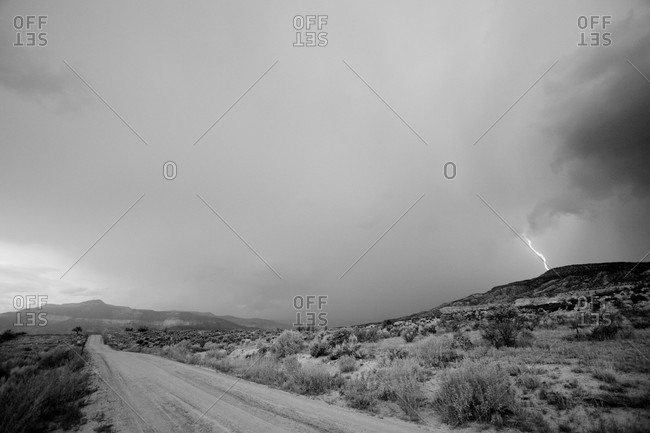Lightning cracks in the distance as seen from a dirt road