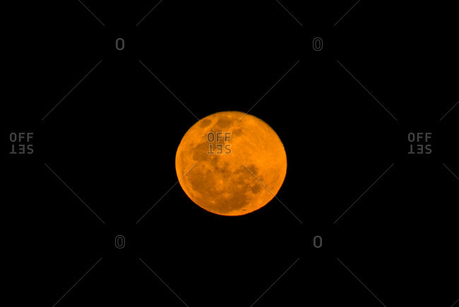 A full moon colored red by atmospheric dust is known as a blood moon