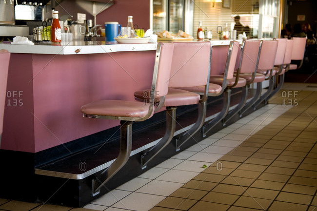 Classic pink chairs line a diner\'s empty counter