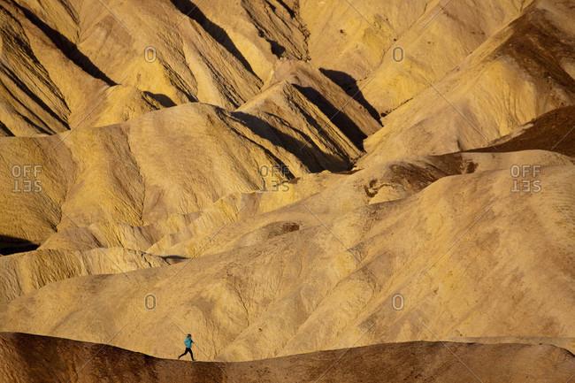 A woman runs along a barren desert ridge near Zabriskie Point
