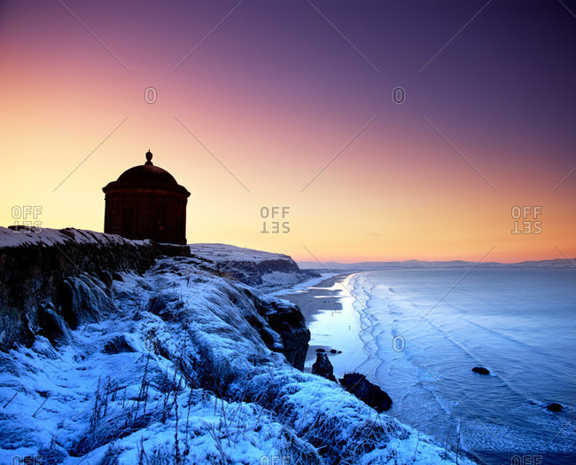 Sunset at Mussenden Temple on snowy cliffs overlooking the beach