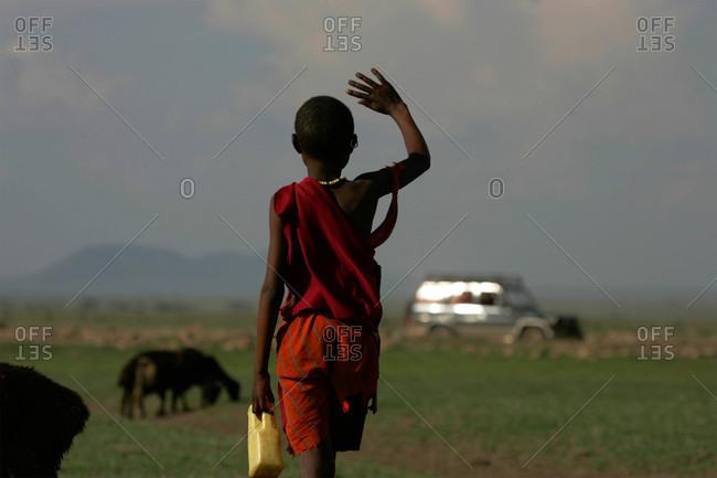 A Masai child waves to tourists