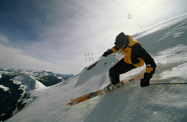An extreme skier races down a sheer slope