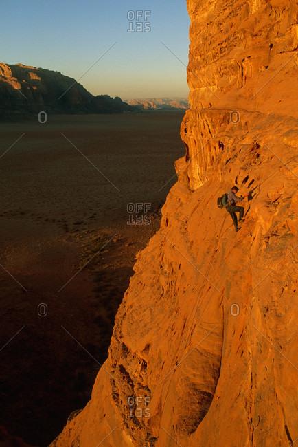 Climber rappels off Jebel [Mount] Khaz Ali, high above desert floor