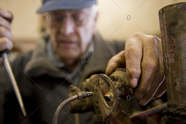 Close up of a man's hands as he works in his tool shop in Cortland, NE