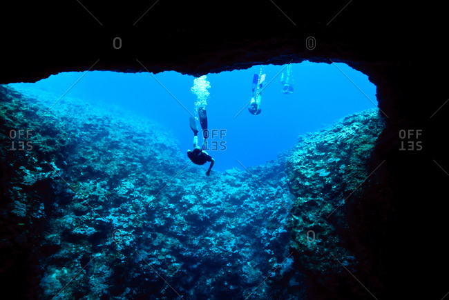 Snorkelers tentatively examine the entrance to an underwater cave