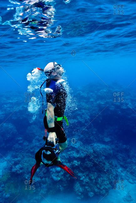 A free diver exhales through his snorkel as he surfaces from the deep