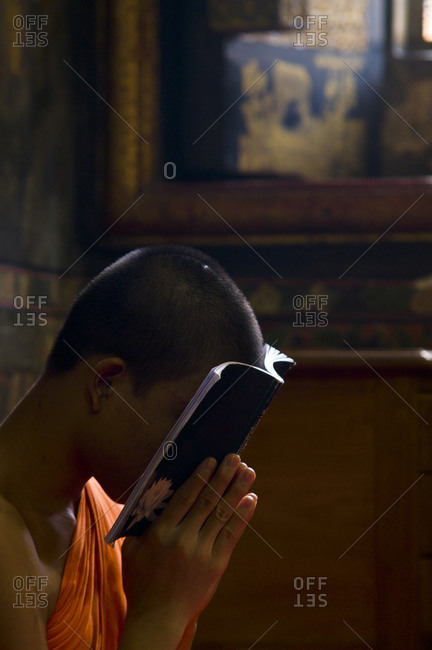 A Buddhist monk in deep prayer in the Ubosot, the temple\'s chapel.