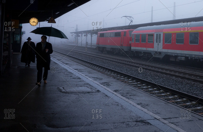 A man with an umbrella at a foggy train station.