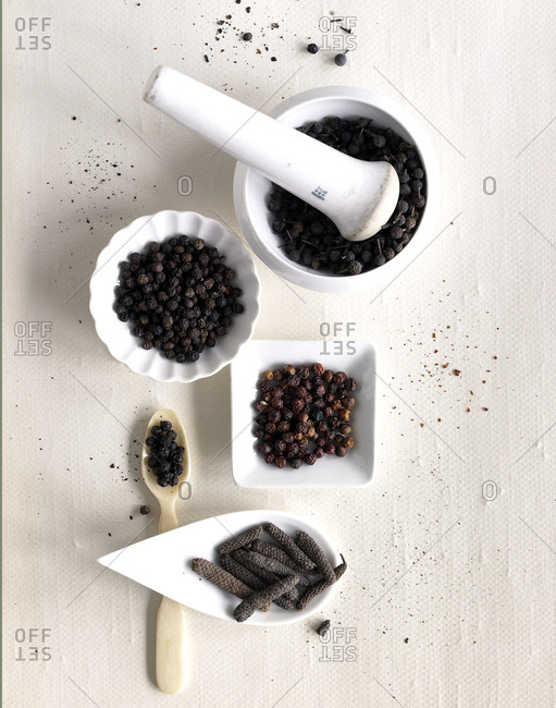 Five types of peppercorns arranged in ramekins on white table