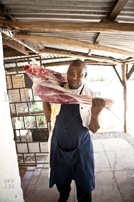 Butcher Carrying Half Lamb Over Shoulder