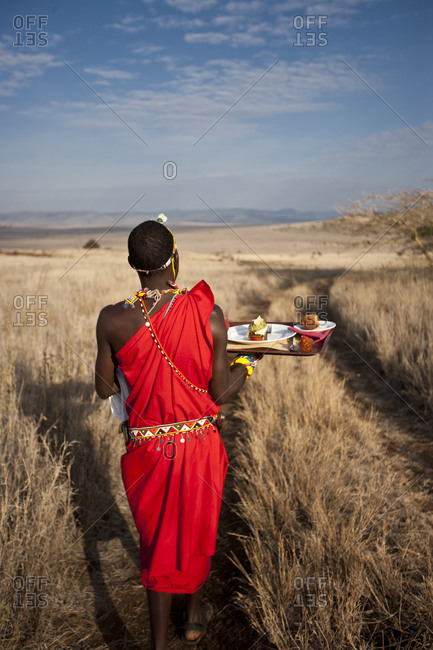 A Massai warrior taking breakfast on a tray in the middle of savannah