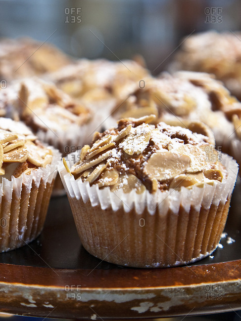 Fresh cupcakes with sliced almonds and powdered sugar topping