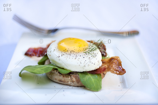 Egg and bacon toast served with spinach leaves