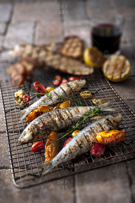 Grilled trout and vegetables served on a rack outdoors