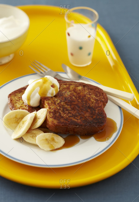 A child's breakfast of French toast topped with maple syrup and whipped cream served with banana slices and a glass of milk