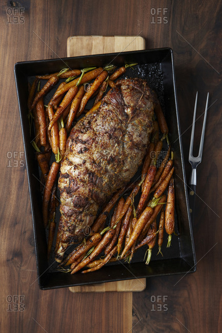 Roasted leg of lamb seasoned and tied together in a pan with roasted carrots