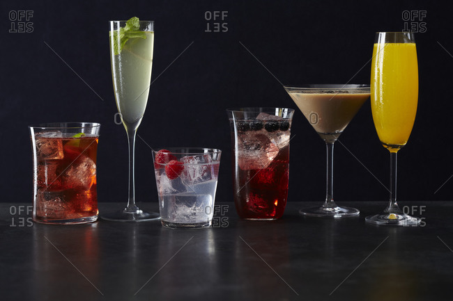 Various of alcoholic cocktails arranged in a row