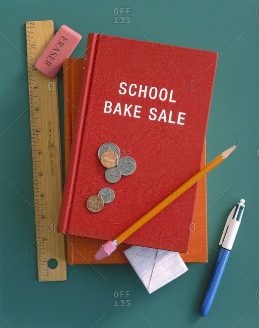 A 'school bake sale' book with a ruler, eraser, pen, pencil, folded piece of paper and coins