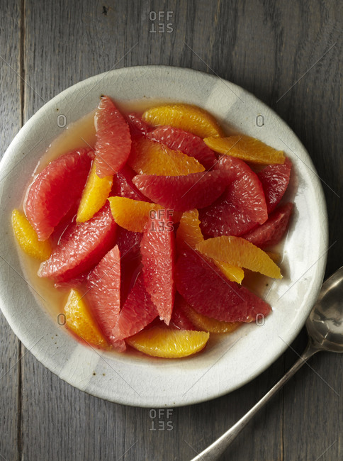 Slices of ruby red grapefruits and navel oranges in fresh fruit juice