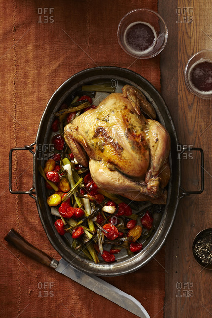 Whole roasted chicken cooked with grape tomatoes, onions, scallions, rosemary and thyme