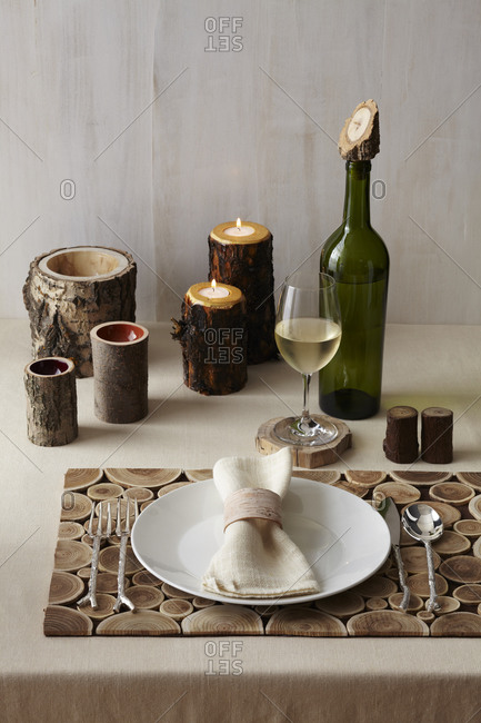 A wood themed table place setting with a wooden place mat, wooden salt and pepper shakers, wooden candle holders, wooden cups, a wooden coaster and a wooden wine corker