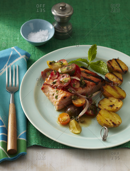Grilled tuna steak garnished with potato stick, and peppermint leaves