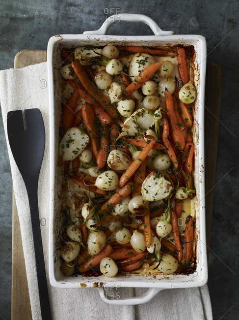 Roasted carrot, pearl onion, radish in a dish, seasoned with finely chopped chives