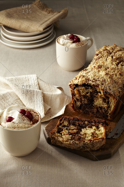 A loaf of chocolate and almond filled babka with cherry coffee topped with whipped cream, cherries and cocoa powder