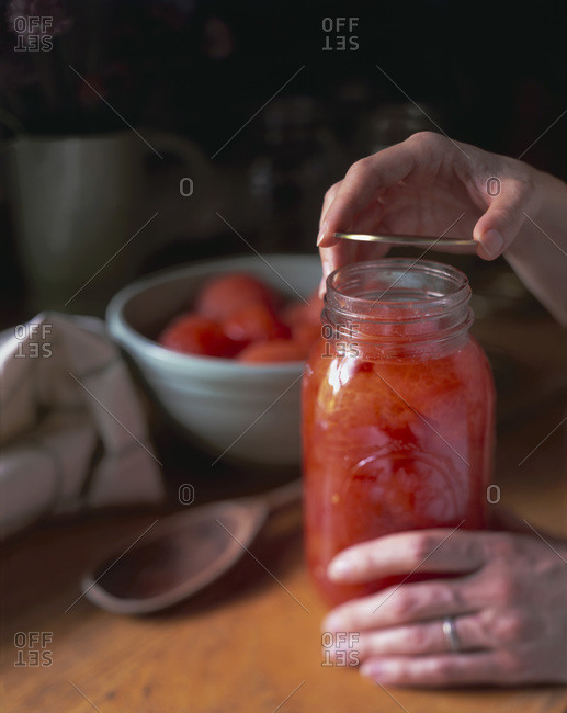 Woman putting lid on jar of canned fruit