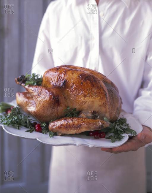 Chef holding a whole roasted turkey