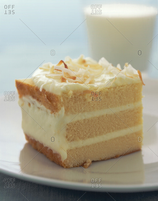 A slice of toasted Coconut Refrigerator cake and a glass of milk