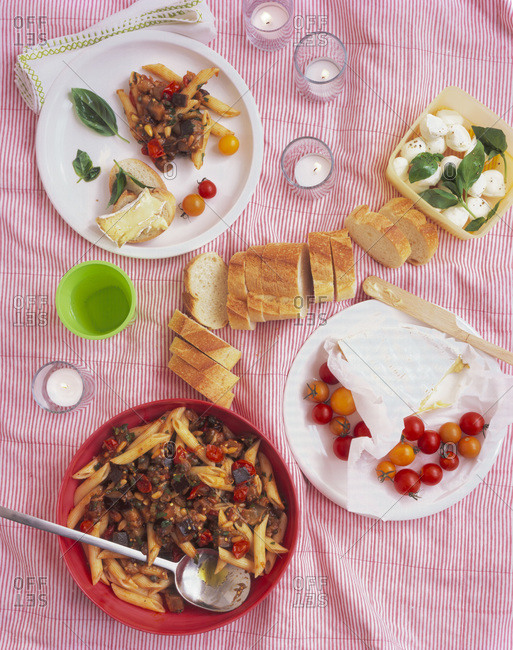 Picnic food spread of pasta salad, cherry tomatoes, a loaf of bread and mozzarella on a blanket with candles