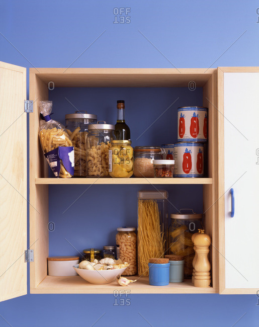 A cabinet full of jars of various pastas, cans of tomato sauce and other ingredients