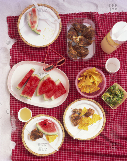 Beach picnic spread: chicken legs, tortilla chips and watermelon slices on a beach blanket