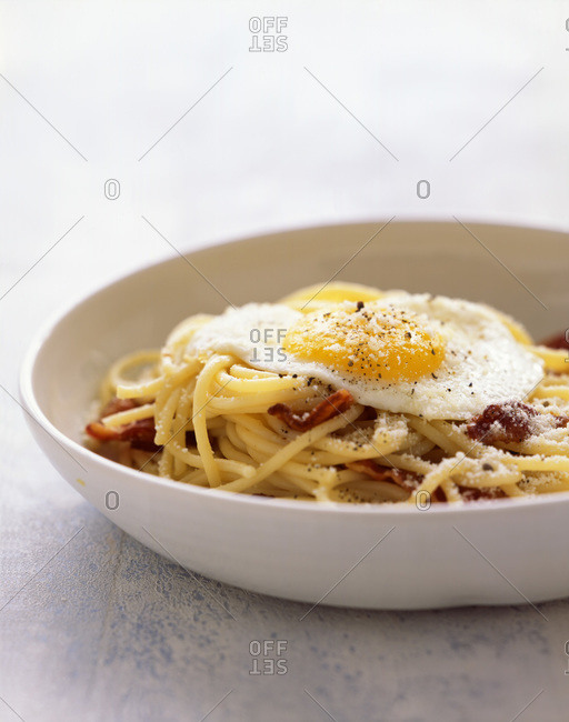 Spaghetti with fried egg and bacon chips