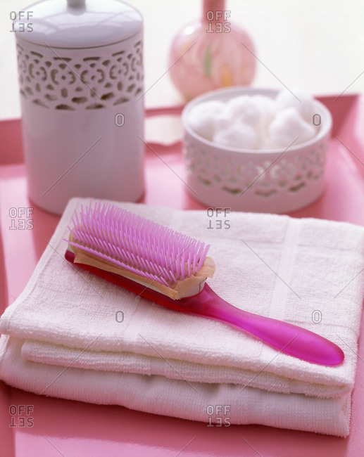 Pink plastic brush on white towels on a pink tray with two containers, one full of cotton balls