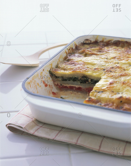 Vegetable lasagna with broccoli and tomatoes in casserole dish