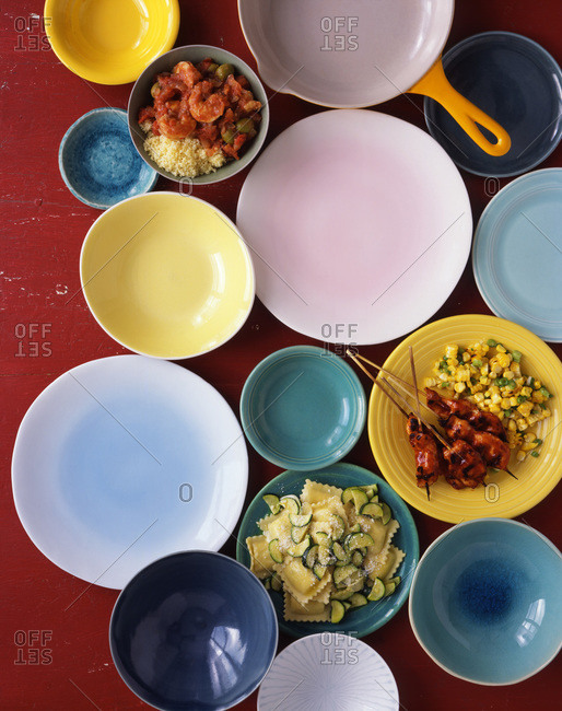 Three plates of food: a plate of bbq chicken on skewers with corn, a plate of ravioli with zucchini and a bowl of shrimp with couscous, surrounded by various colored and sized empty plates and bowls