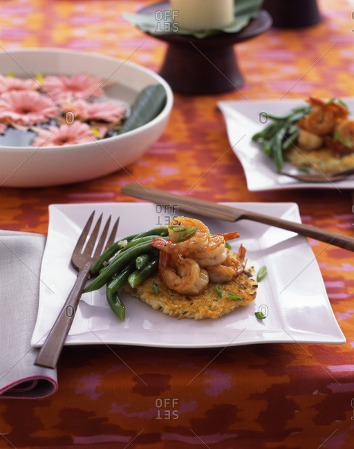 A plate of shrimp and green beans on top of a rice cake with a wooden fork and knife and a bowl of floating pink flowers