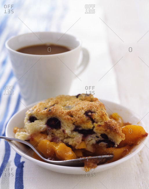 A plate with a blueberry scone and peaches in a sugar served with a cup of coffee for breakfast