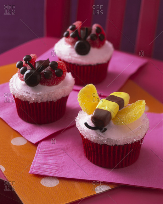 Three cupcakes with edible candy bumblebees and ladybugs on top