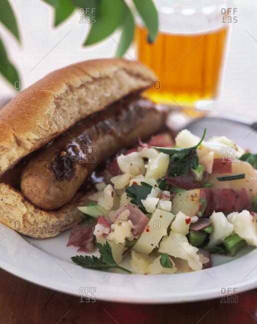 Sausage in bun and potato salad