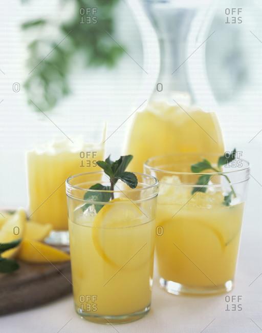 Three glasses and a decanter of fresh lemonade