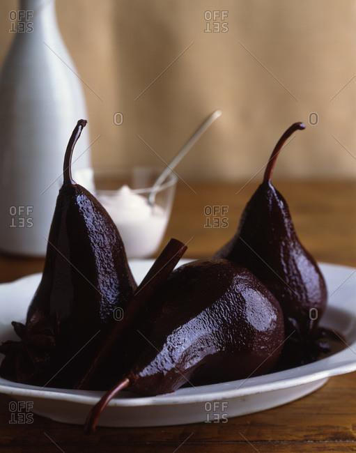 Merlot-poached pears with vanilla-cinnamon yogurt in the background