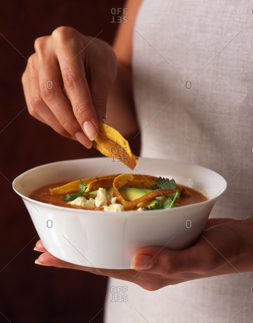 Woman holding a bowl of spicy Mexican tortilla soup topped with tortilla strips