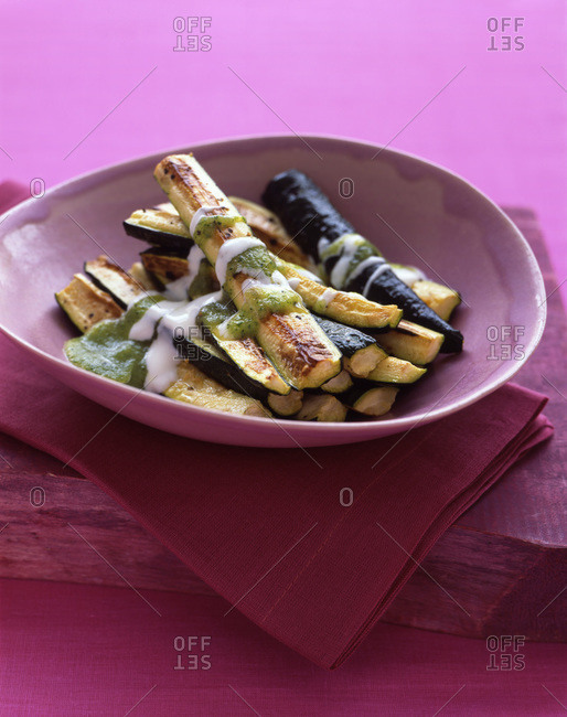 Roasted zucchini sticks drizzled with sauce for an appetizer or side dish