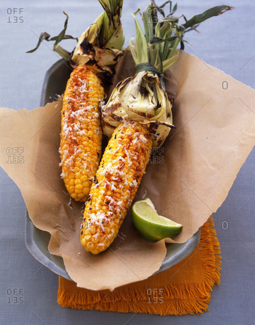 Grilled corn overhead with a lime wedge